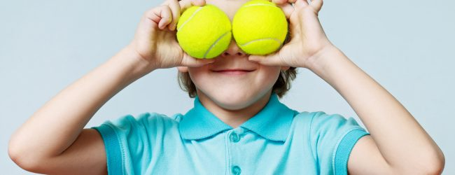 Little boy holding tennis balls instead of the eyes, smiling